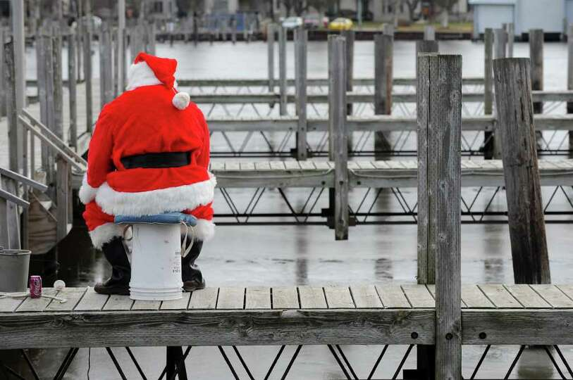 A man dressed as Santa fishes for perch through the ice on the docks at Lakeside Park in Fond du Lac