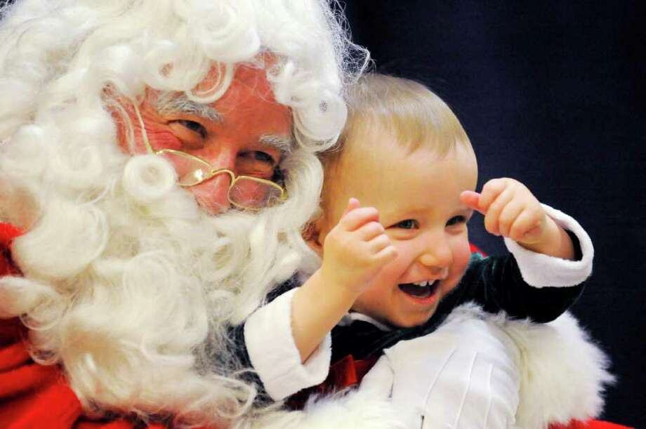 Bill Trochil, portraying Santa Claus, hugs Samantha Munden, 1, both of Manitowoc, as they pose for pictures at the Manitowoc Public Library in Manitowoc, Wis. Photo: Matthew Apgar, Associated Press / Herald Times Reporter
