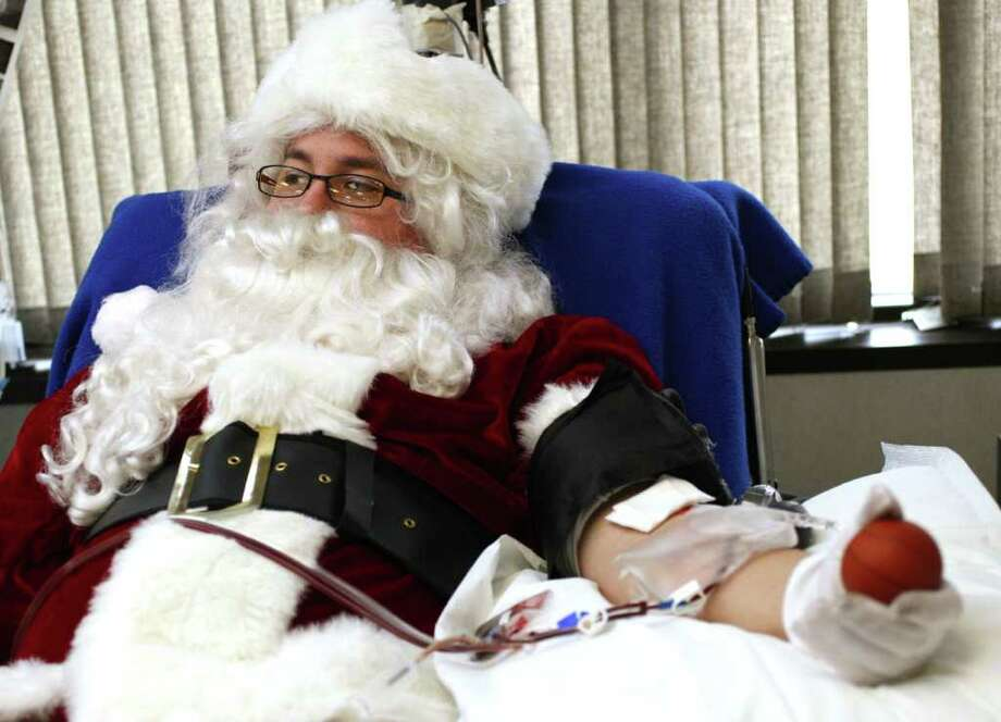 William Hawkins wears a Santa suit to give blood  through an apheresis procedure, where blood platelets are donated, at the Tulsa Red Cross. Photo: Cory Young, Associated Press / The Tulsa World