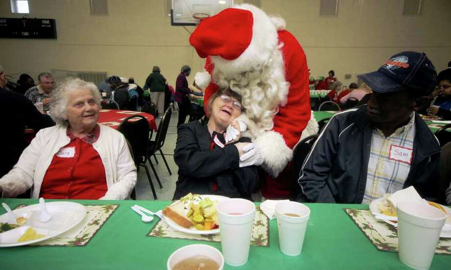 Santa shares a little love with guest attending the You are a Blessing Christmas party at Mount Sinai Baptist Church in Cleveland County, North Carolina. Photo: Brittany Randolph, Associated Press / The Star