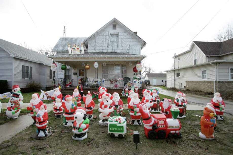 More than a dozen of plastic Santas have turned a soggy neighborhood yard into the North Pole, Wednesday, Dec. 21, 2011, in North Baltimore, Ohio. Photo: J.D. Pooley, Associated Press / Sentinel-Tribune
