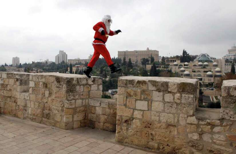 A Palestinian man dressed-up in a Santa Claus costume walks on Jerusalem's Old City walls on Decembe