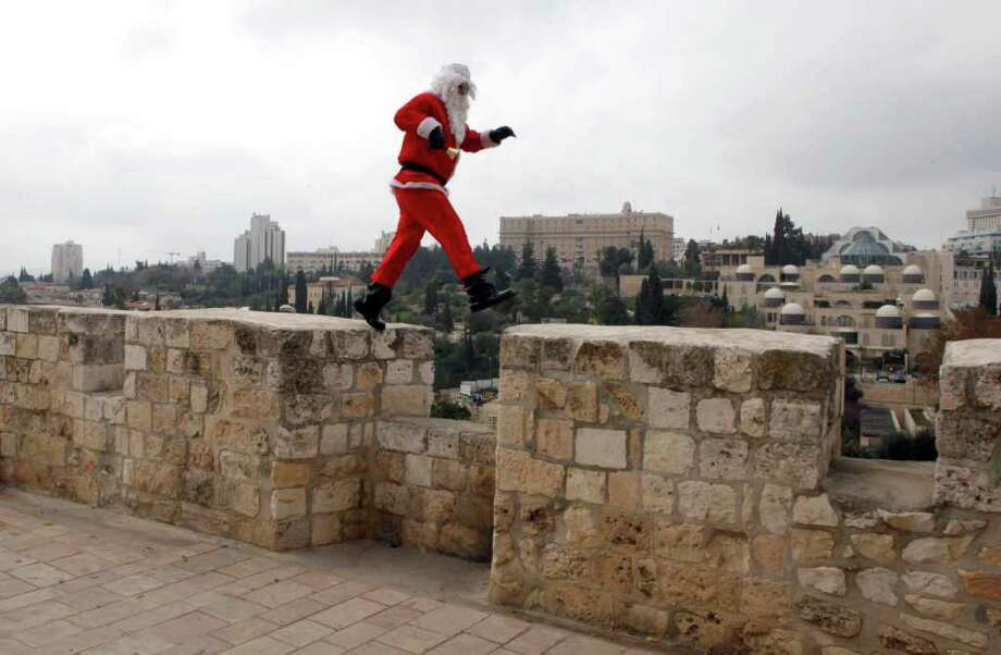 A Palestinian man dressed-up in a Santa Claus costume walks on Jerusalem's Old City walls on December 21, 2011 few days ahead of Christmas. Photo: GALI TIBBON, Getty / AFP