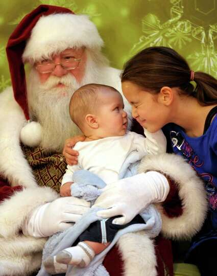 Liam Villa, 5 months, grabs his sister Gabrielle's face as they sit for a photo with Santa, played b
