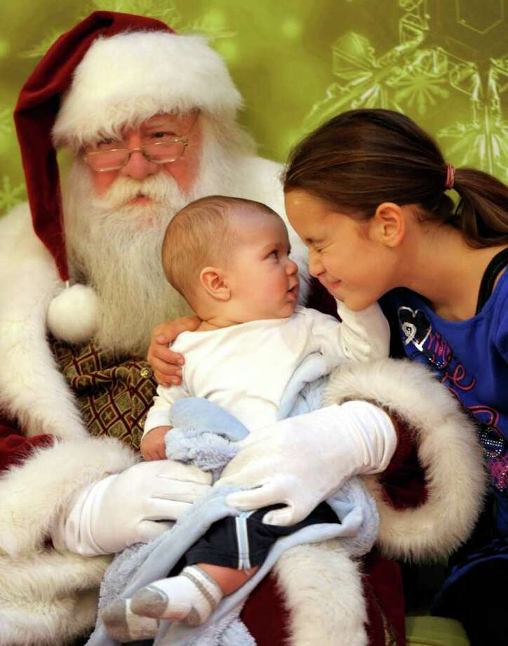 Liam Villa, 5 months, grabs his sister Gabrielle's face as they sit for a photo with Santa, played by Dave Puffer, at the Crystal Mall in Waterford, Conn. Photo: Sean D. Elliot, Associated Press / 2011 The Day Publishing Company
