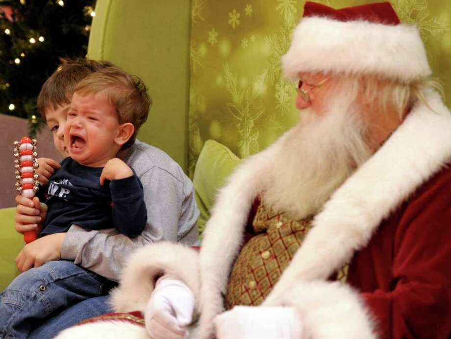 Chase Costa, 17 months, breaks into tears sitting on the lap of his brother Tristan, 8, as they visit Santa, played by Dave Puffer, at the Crystal Mall in Waterford, Conn. Photo: Sean D. Elliot, Associated Press / 2011 The Day Publishing Company