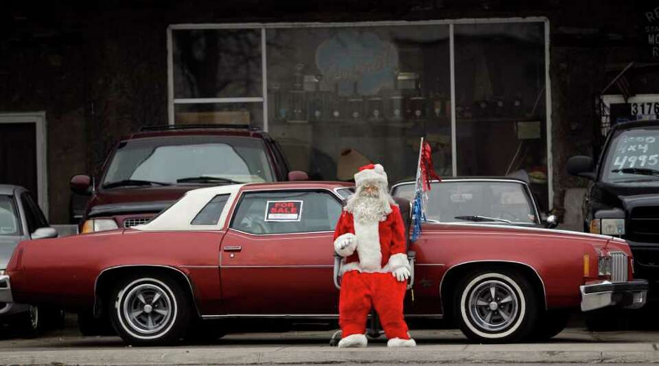 A used car lot is decorated for the holiday season with a Santa Claus display in Buffalo, N.Y., Mond