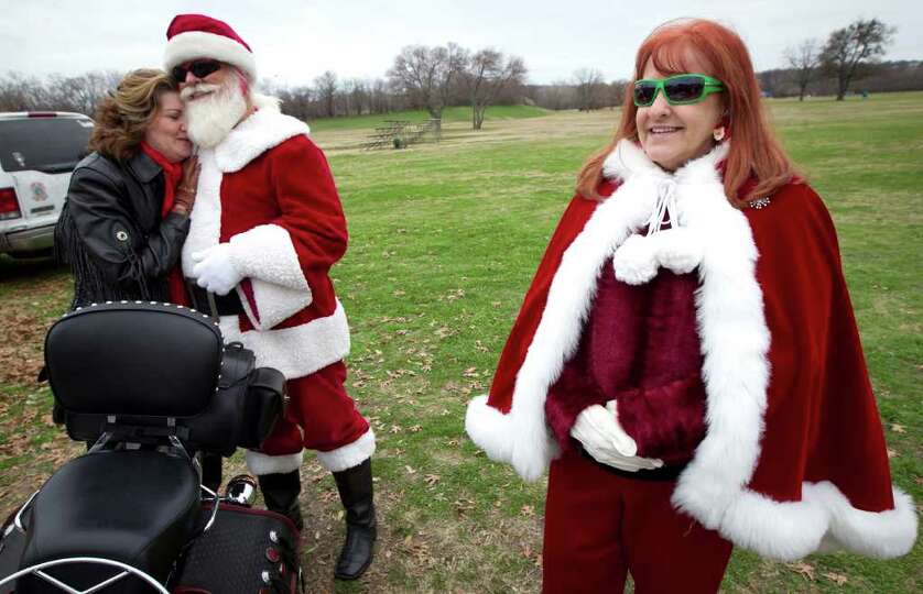 Rhonda Newsome, of Fort Worth, Texas, hugs Mike Richardson, dressed as Santa, while he and his wife,