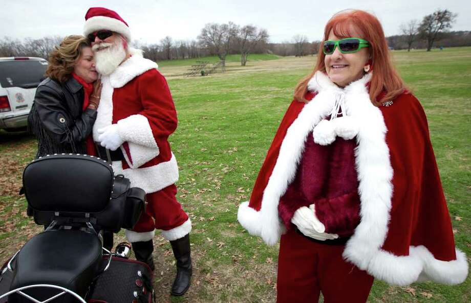 Rhonda Newsome, of Fort Worth, Texas, hugs Mike Richardson, dressed as Santa, while he and his wife, Anne, greet motorcyclists at Gateway Park in Fort Worth while organizing for the annual Big Texas Toy Run ending at Quick Trip Park in Grand Prairie, Texa. Photo: Joyce Marshall, Associated Press / Fort Worth Star-Telegram