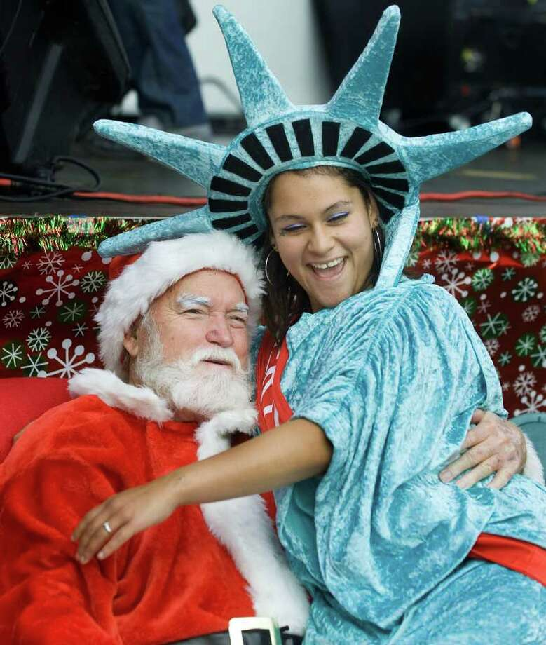 Candace Vallarta, dressed as the Statue of Liberty, meets a man dressed as Santa Claus, during the 4th Annual Toy Drive in the Barrio, at Jerome Park in Santa Ana, Calif. Photo: Mindy Schauer, Associated Press / THE ORANGE COUNTY REGISTER