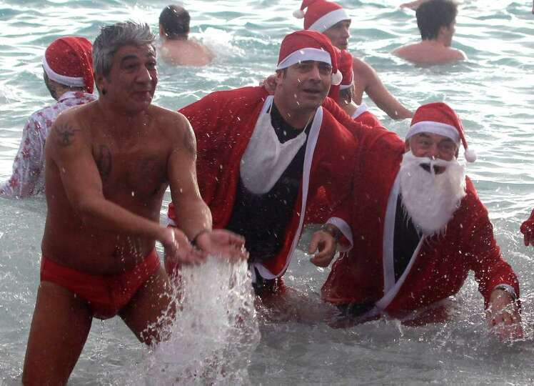 Men dressed as Santa Claus swim in the Mediterranean sea in Monaco, Sunday, Dec. 18, 2011, during th