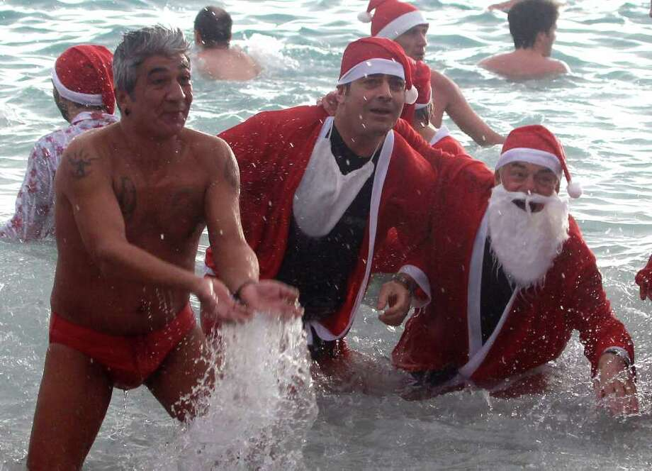 Men dressed as Santa Claus swim in the Mediterranean sea in Monaco, Sunday, Dec. 18, 2011, during the traditional Christmas bath. Photo: Lionel Cironneau, Associated Press / AP
