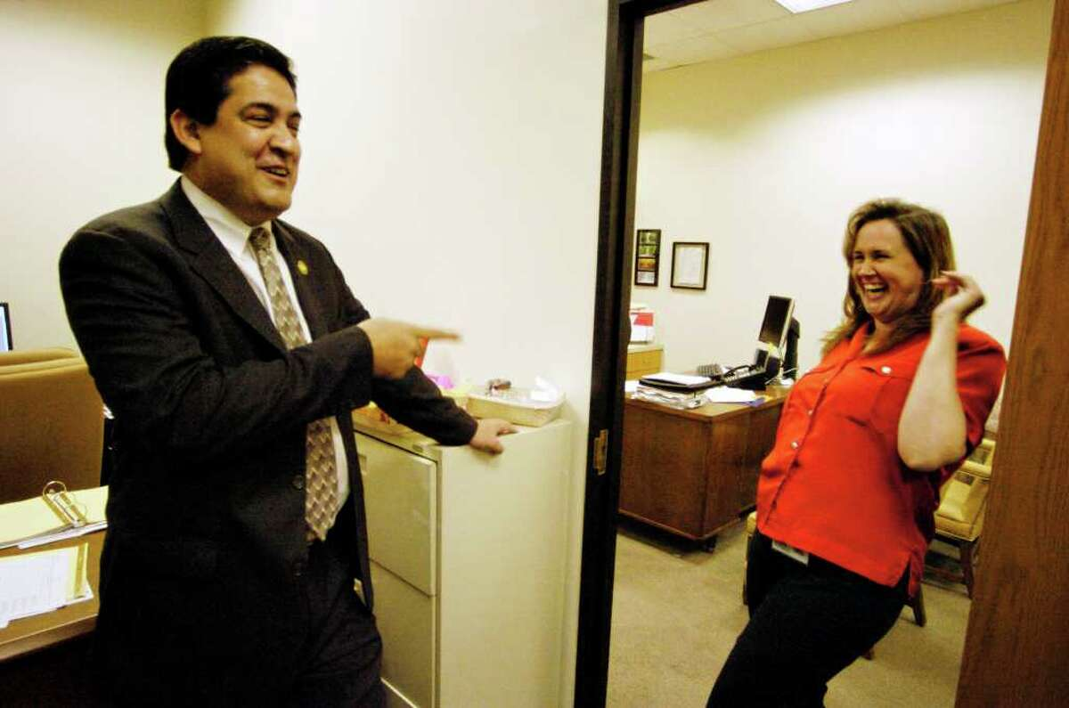 David Marquez, economic development chief for Bexar County jokes with Virginia Kelley, his assistant, on her first day back to work at Economic Development and Special Programs for Bexar County after her otosclerosis surgery one week prior, Wednesday, July 26, 2006.