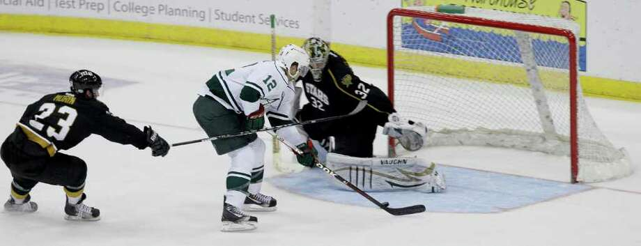 12/21/11: Houston Aeros Cody Almond (12) makes a move and scores on Texas Stars Tyler Beskorowany (32) while Texas Stars Travis Morin (23) gives chase in the second period of a hockey game at Toyota Center in Houston, Texas. Photo: Thomas B. Shea, For The Chronicle / © 2011 Thomas B. Shea