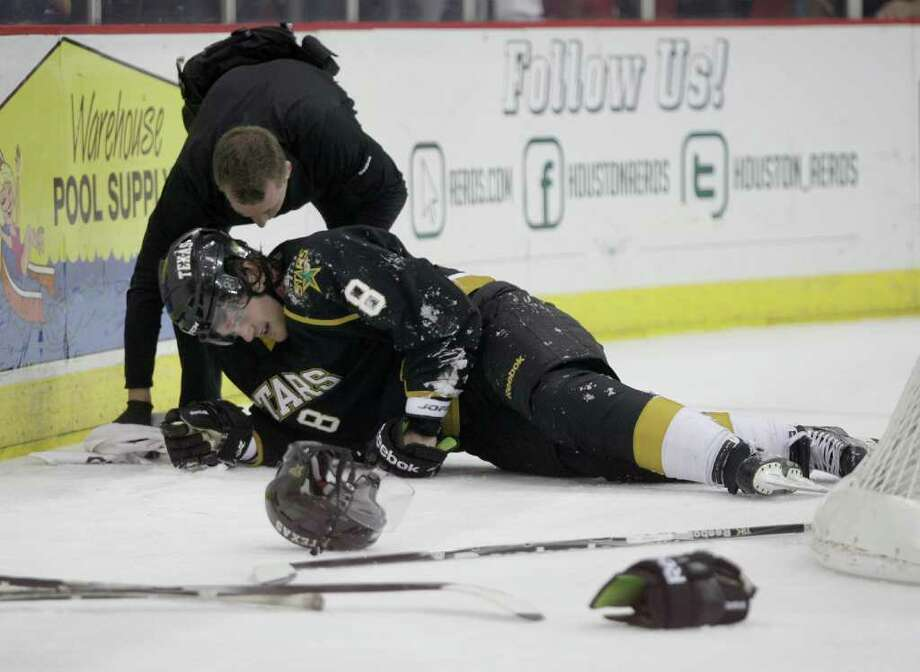 12/21/11: Texas Stars Jordie Benn (8) lays on the ice injured after a hard check by an Houston Aero in the first period of a hockey game at Toyota Center in Houston, Texas. Photo: Thomas B. Shea, For The Chronicle / © 2011 Thomas B. Shea