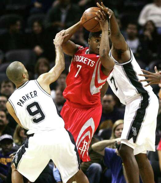 Houston Rockets' Kyle Lowry (7) is double-teamed by San Antonio Spurs' Tony Parker (9) and Gani Lawa