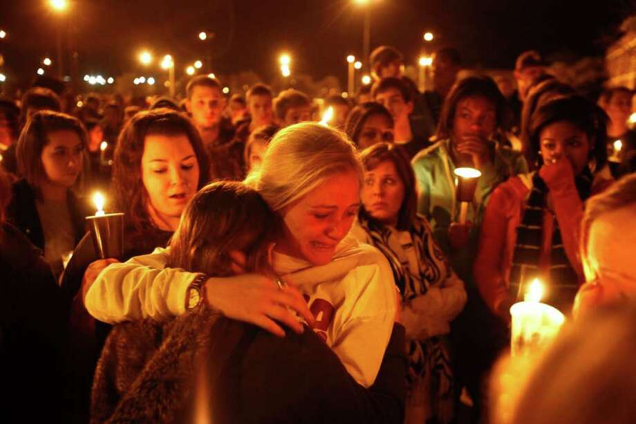 Tyler Reichart gets a hug during a candlelight vigil for Cinco Ranch basketball player Chris Saiz who died last night in an auto accident at a gathering at the Cinco Ranch High Schoo in Katy. Photo: Michael Paulsen, Houston Chronicle / © 2011 Houston Chronicle