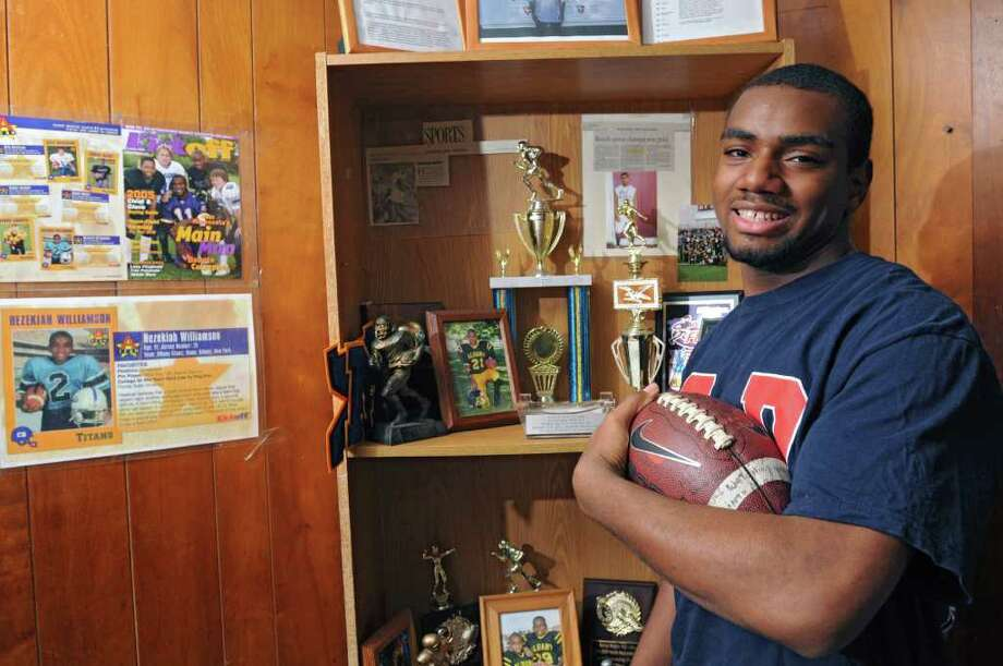 Albany High School football player Hezekiah Williamson stands next to his trophies in his home on Tuesday, Dec. 6, 2011 in Albany, N.Y. (Lori Van Buren / Times Union) Photo: Lori Van Buren