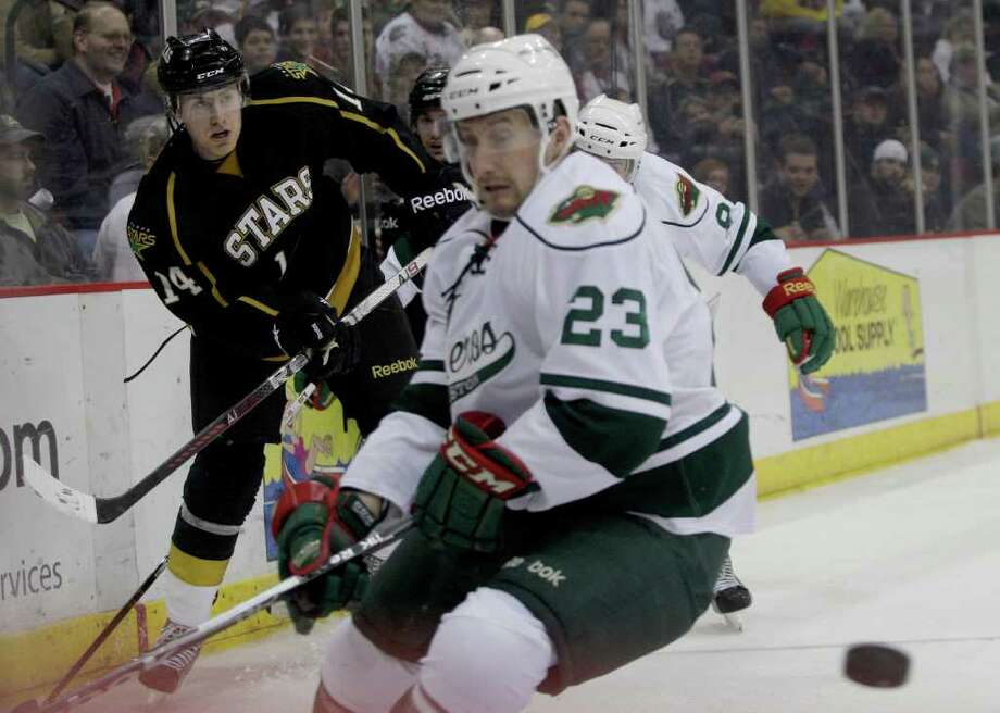12/21/11: Texas Stars Stephen Schultz (14) shoots the puck around the boards in front of Houston Aeros Harrison Reed (23) in the third period in a hockey game at Toyota Center in Houston, Texas. The Aeros loss 3 to 2. Photo: Thomas B. Shea, For The Chronicle / © 2011 Thomas B. Shea