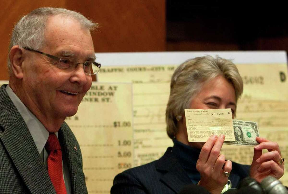 Dale Crawford, left, and Mayor Annise Parker, right, laugh as she holds a 58-year-old parking ticket issued to Crawford and $1.00 to pay it during a press conference at City Hall Wednesday, Dec. 21, 2011, in Houston. Crawford received the ticket on Feb. 3, 1953, the day he was inducted into the U.S. Army when he left his 1946 Nash at the induction station where his father arrived late to pick it up. Crawford wrote to the city,