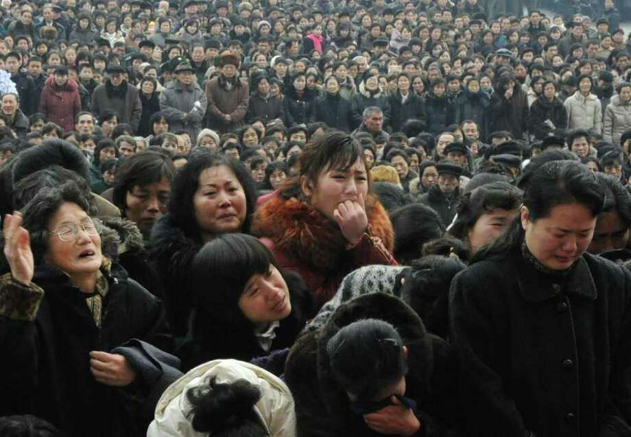 Pyongyang citizens grieve as they visit a portrait of late North Korean leader Kim Jong Il at Kim Il Sung Square in Pyongyang, North Korea, Wednesday, Dec. 21, 2011. (AP Photo/Kyodo News) JAPAN OUT, MANDATORY CREDIT, NO LICENSING IN CHINA, FRANCE, HONG KONG, JAPAN AND SOUTH KOREA