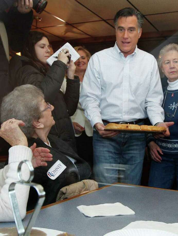 Republican presidential candidate former Mass. Gov. Mitt Romney delivers a pizza to patrons while campaigning at Village Pizza in Newport, N.H., Wednesday Dec. 20, 2011. (AP Photo/Charles Krupa) Photo: Charles Krupa