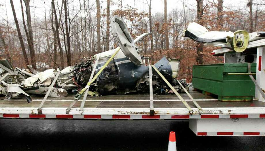 Debris from a plane that crashed on the highway Tuesday are seen on a flatbed truck, Wednesday, Dec. 21, 2011, in Morris Township, N.J. The high-performance Socata TBM-700 turboprop spun out of control and crashed, killing all five people aboard and narrowly avoiding dozens of cars and trucks on Highway 287. Federal investigators are searching for debris, which was scattered over at least a half-mile, with one section found lodged in a tree a quarter-mile away. ( AP Photo/Julio Cortez) Photo: Julio Cortez