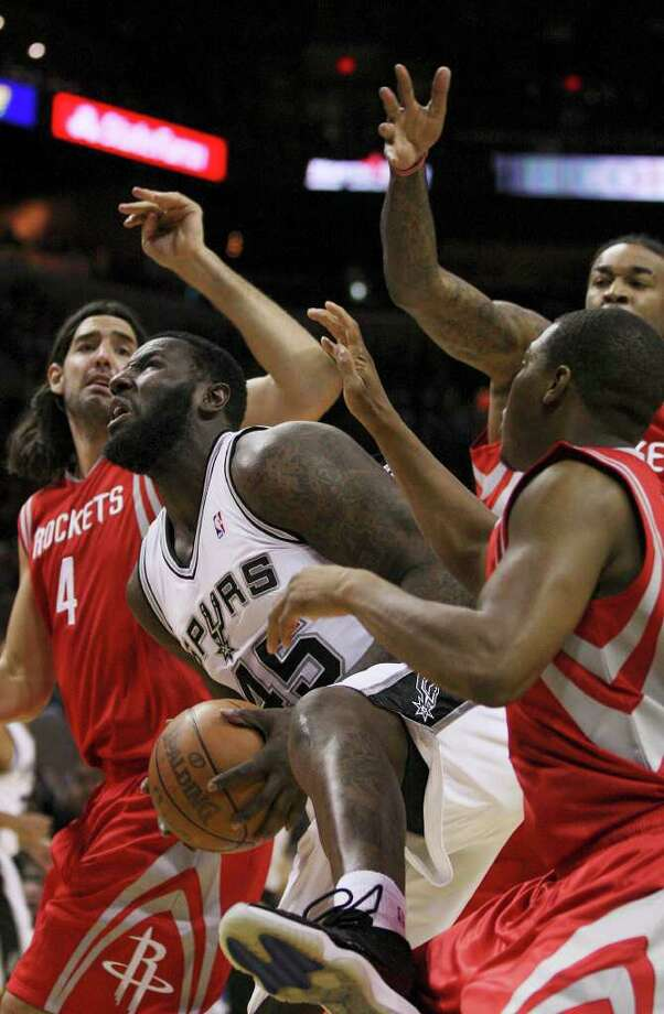 Surrounded by Houston Rockets players, San Antonio Spurs center DeJuan Blair pulls in a rebound during the first half of an NBA preseason game at the AT&T Center in San Antonio, Wednesday, Dec. 21, 2011. The Rockets are from left, forward Luis Scola, center Jordan Hill and guard Kyle Lowry. JERRY LARA/glara@express-news.net Photo: JERRY LARA, Express-News / SAN ANTONIO EXPRESS-NEWS