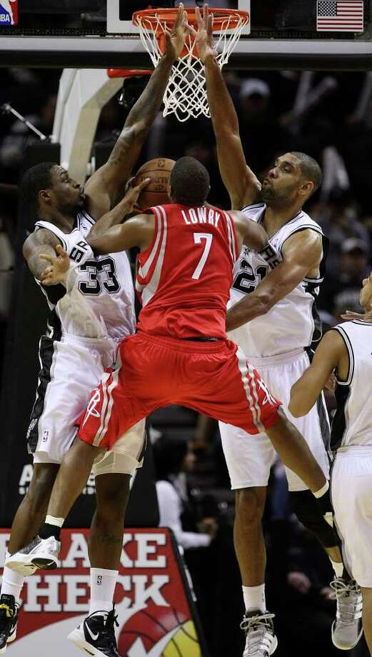 San Antonio Spurs forwards Frank Hassell, left, and Tim Duncan block Houston Rockets guard Kyle Lowry during the second half of an NBA preseason game at the AT&T Center in San Antonio, Wednesday, Dec. 21, 2011. The Spurs won 97-95. JERRY LARA/glara@express-news.net Photo: JERRY LARA, Express-News / SAN ANTONIO EXPRESS-NEWS
