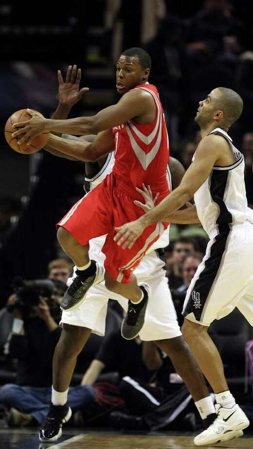 Houston Rockets guard Kyle Lowry passes around San Antonio Spurs guard Tony Parker during the first half of an NBA preseason game at the AT&T Center in San Antonio, Wednesday, Dec. 21, 2011. JERRY LARA/glara@express-news.net Photo: JERRY LARA, Express-News / SAN ANTONIO EXPRESS-NEWS