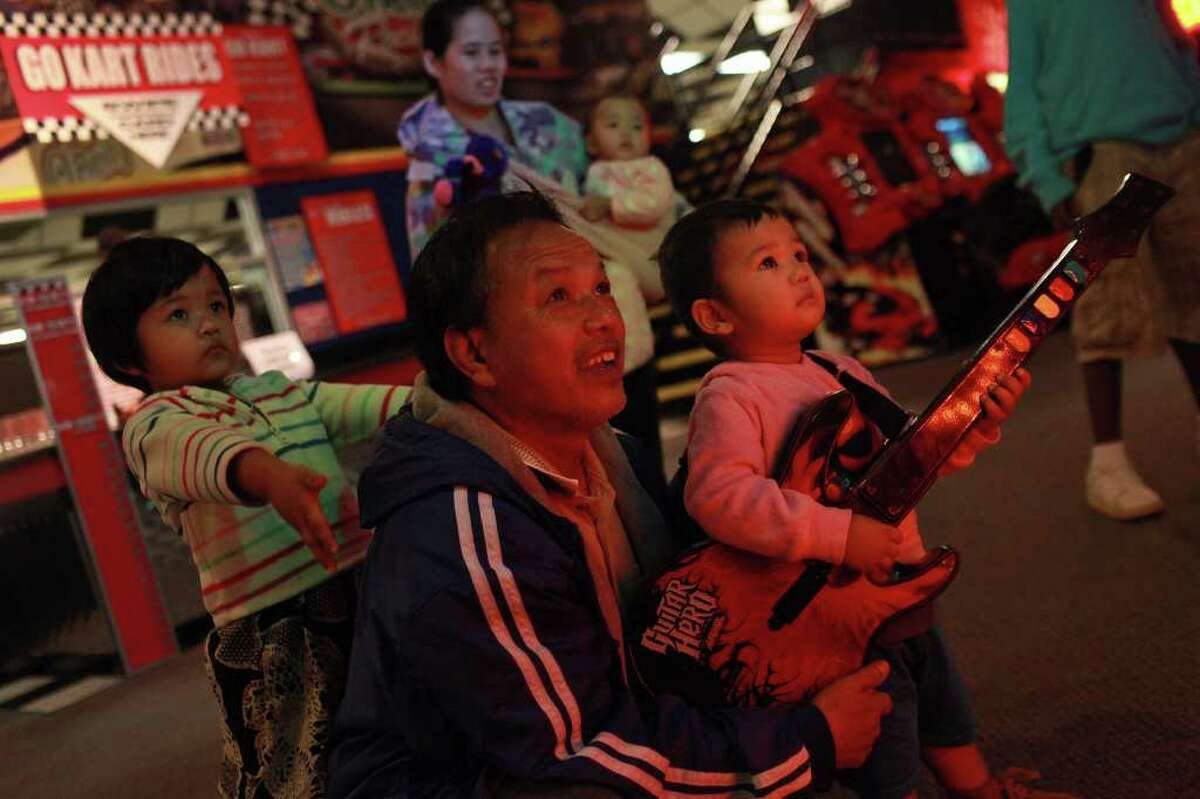 Vanapa Fam Cun plays Guitar Hero with his children, Ronal, 18 months (right), and Julia, 3 (left), during a holiday party for refugees with Catholic Charities and American Opportunity for Housing at Incredible Pizza Company on Wednesday, Dec. 21, 2011.