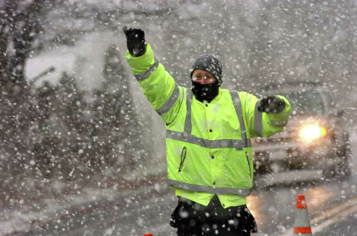 As the snow flies, Amdi Suli, of Superior Traffic Control out of Waterbury, directs traffic around a tree removal crew along Edgefield Avenue in Milford, Conn. on Friday January 7, 2011.