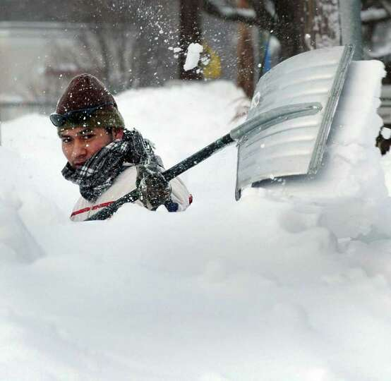 After hours of snowfall,Franceso Mateo clears the sidewalk in front of Penny's II Diner on Black Roc