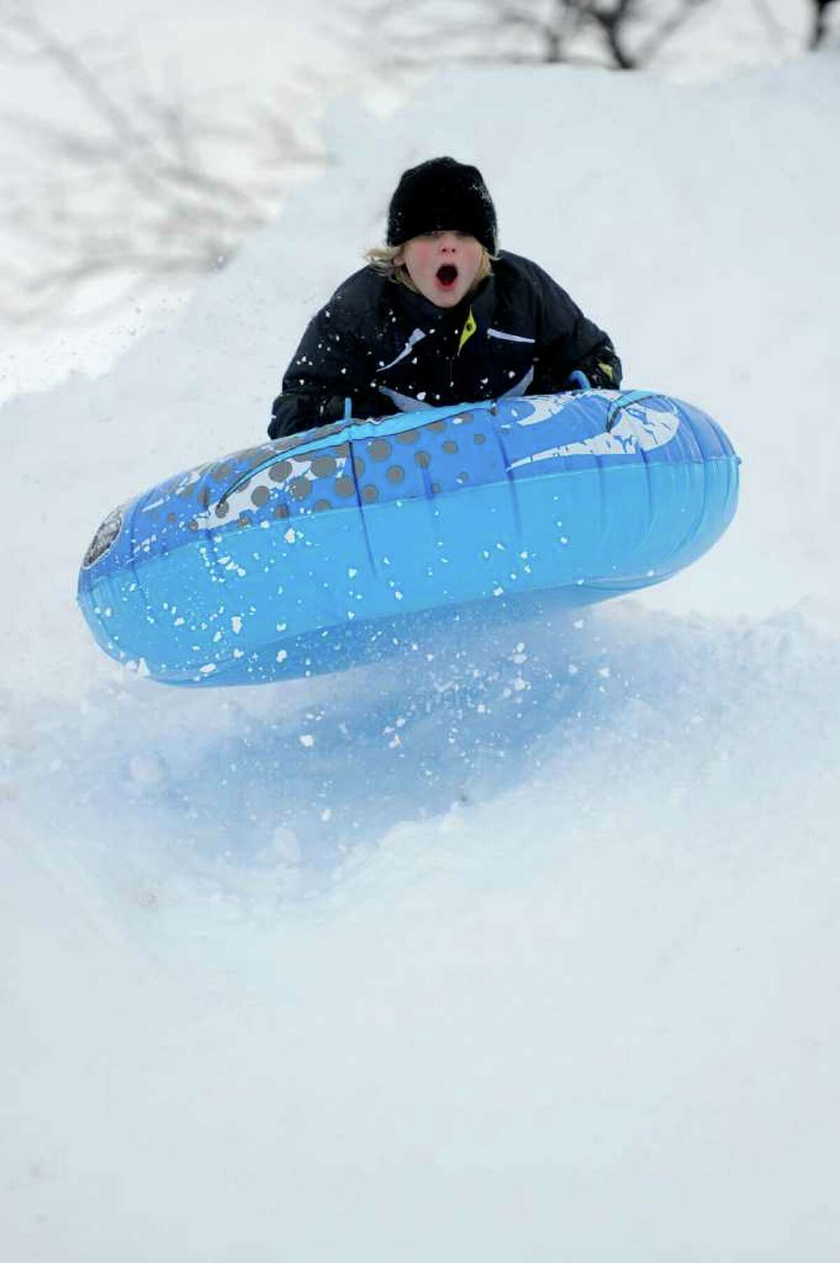 Christopher Puchala, 11, catches some air as he sleds off a giant mound of snow created by plows in the parking lot behind Greensfarms Elementary School in Westport on Wednesday, January 12, 2011.