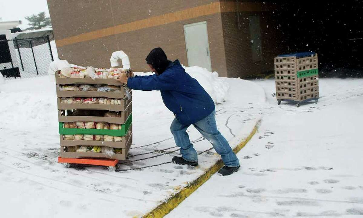 A delivery man struggles through the new snow at Stop & Shop as another winter storm hits the area in Stamford, Conn. on Tuesday February 1, 2011.