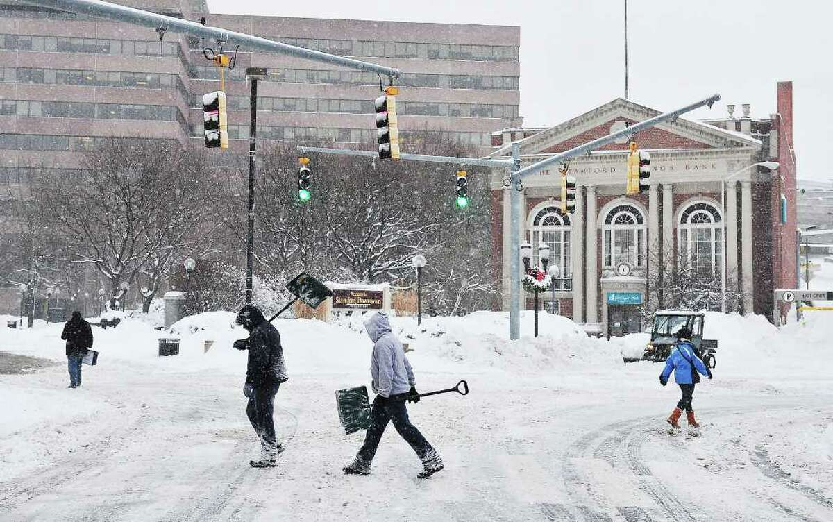 Pedestrians and plows occupied the streets Wednesday morning in downtown Stamford.