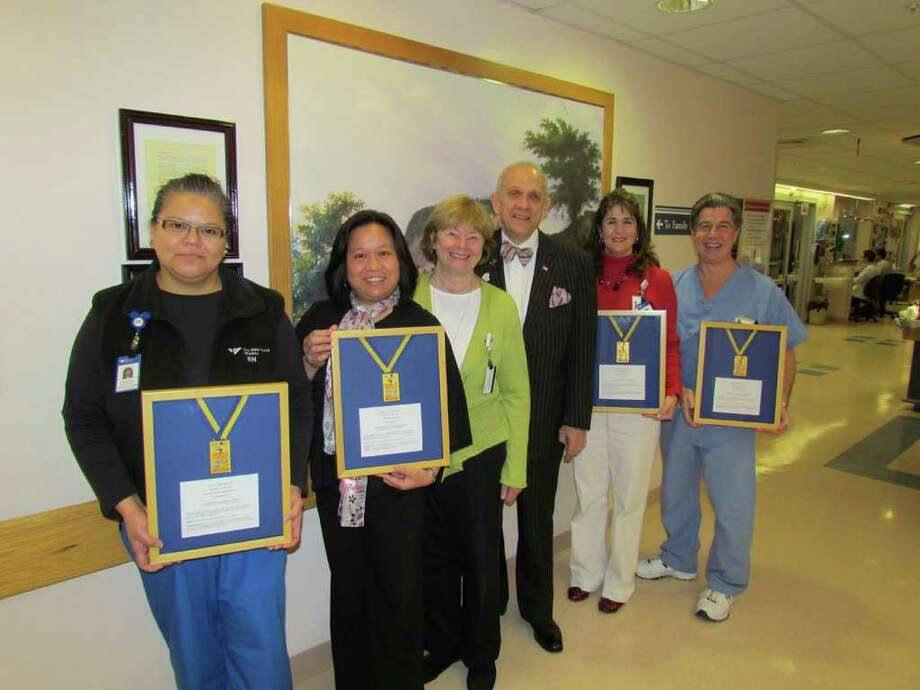 From left, holding the World Transplant Games gold medals are members of the Yale-New Haven Hospital Heart and Vascular Center care team: Chris Santiago, RN; Noreen Gorero, RN; Cathy and Pete Kenyon; Laurie Devin, RN; and Edward Rocco, perfusionist. Photo: Contributed Photo