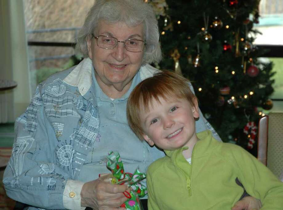 Jayden Grayson presents a handmade holiday gift to Mildred, a New Canaan Inn resident. Photo: Contributed Photo
