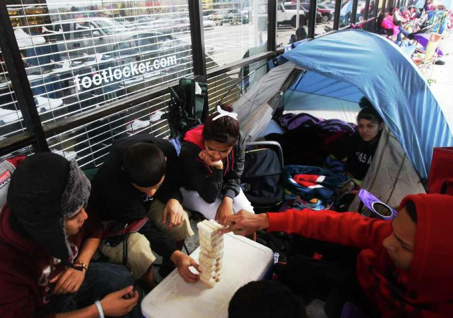 Clockwise from left, Diego Noria, Benjy Zul, Alexis Ramirez, Chelsea Soto and Chris Saucedo play Jenga as they wait for Foot Locker to open at Gulf Gate mall. Customers began to line up as early as yesterday afternoon for the release of the new Air Jordans. Photo: Cody Duty / Houston Chronicle