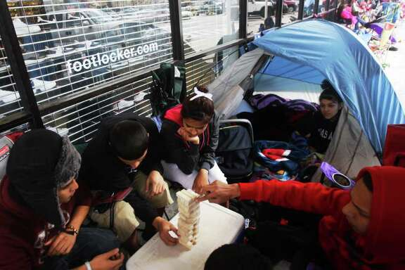 Clockwise from left, Diego Noria, Benjy Zul, Alexis Ramirez, Chelsea Soto and Chris Saucedo play Jenga as they wait for Foot Locker to open at Gulf Gate mall. Customers began to line up as early as yesterday afternoon for the release of the new Air Jordans.