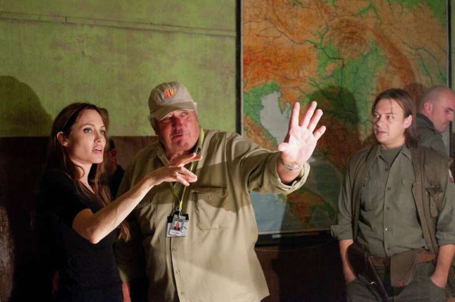"In this image released by Film District, writer-director Angelina Jolie, left, speaks with the director of photography Dean Semler, center, during the filming of ""In the Land of Blood and Honey."" Photo: FILM DISTRICT"