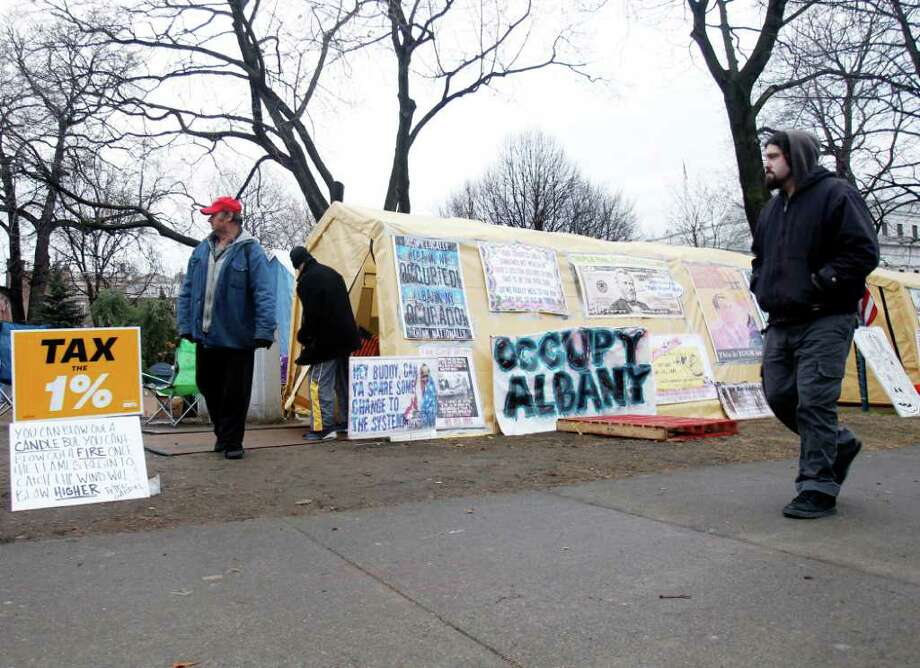 Occupy Albany protesters walk in Academy Park in Albany, N.Y., on Thursday, Dec. 22, 2011. Occupy Albany's 24-hour permit for the park expired at 7 a.m. on Thursday but protesters and tents remained in the park. The group had events planned later in the day. (AP Photo/Mike Groll) Photo: Mike Groll