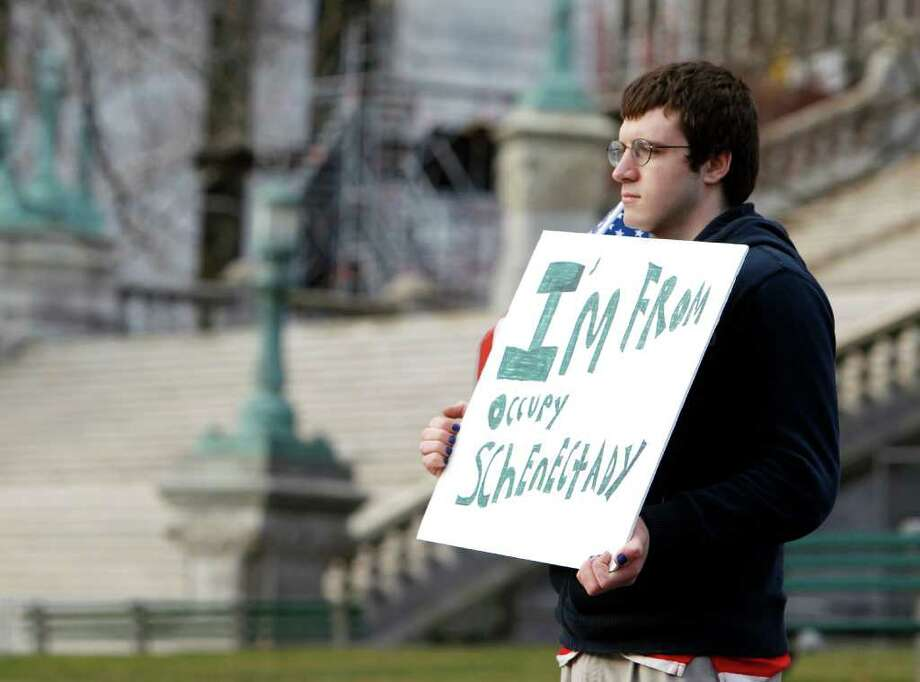 Occupy Schenectady protester Anthony Hadden of Schenectady, N.Y., holds a sign near Occupy Albany's site in Academy Park in Albany, N.Y., Thursday, Dec. 22, 2011. Occupy Albany's 24-hour permit for the park expired at 7 a.m. on Thursday but protesters and tents remained in the park. The group had events planned later in the day. (AP Photo/Mike Groll) Photo: Mike Groll