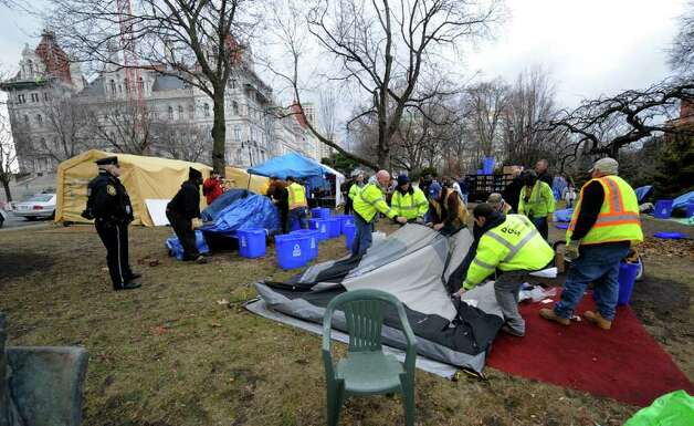 Under the watchful eye of the Albany Police, members of the Albany Department of General Services remove the tents and anything related to the encampment of Occupy Albany from Academy Park in Albany, N.Y. Dec. 22, 2011.     (Skip Dickstein / Times Union) Photo: SKIP DICKSTEIN