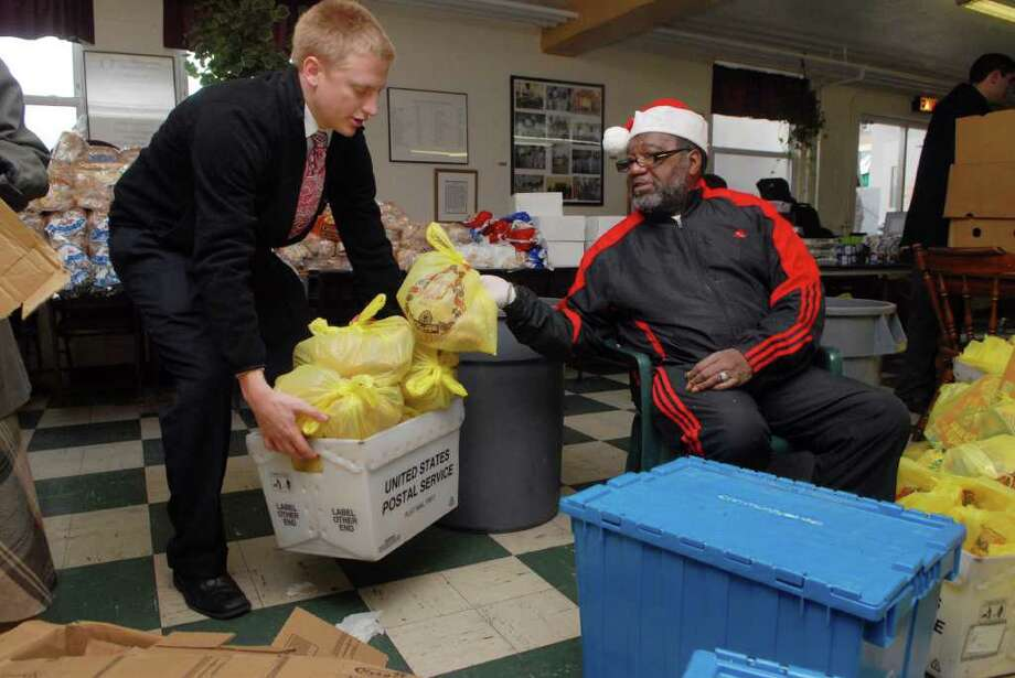 Volunteers Jordan Johnson, a missionary from the Mormon Church, and Harold McCore package donations getting ready to open the 164 Wilson Food Pantry on Richmond Hill Ave in Stamford, Conn. to clients on Thursday December 22, 2011. Photo: Dru Nadler / Stamford Advocate Freelance
