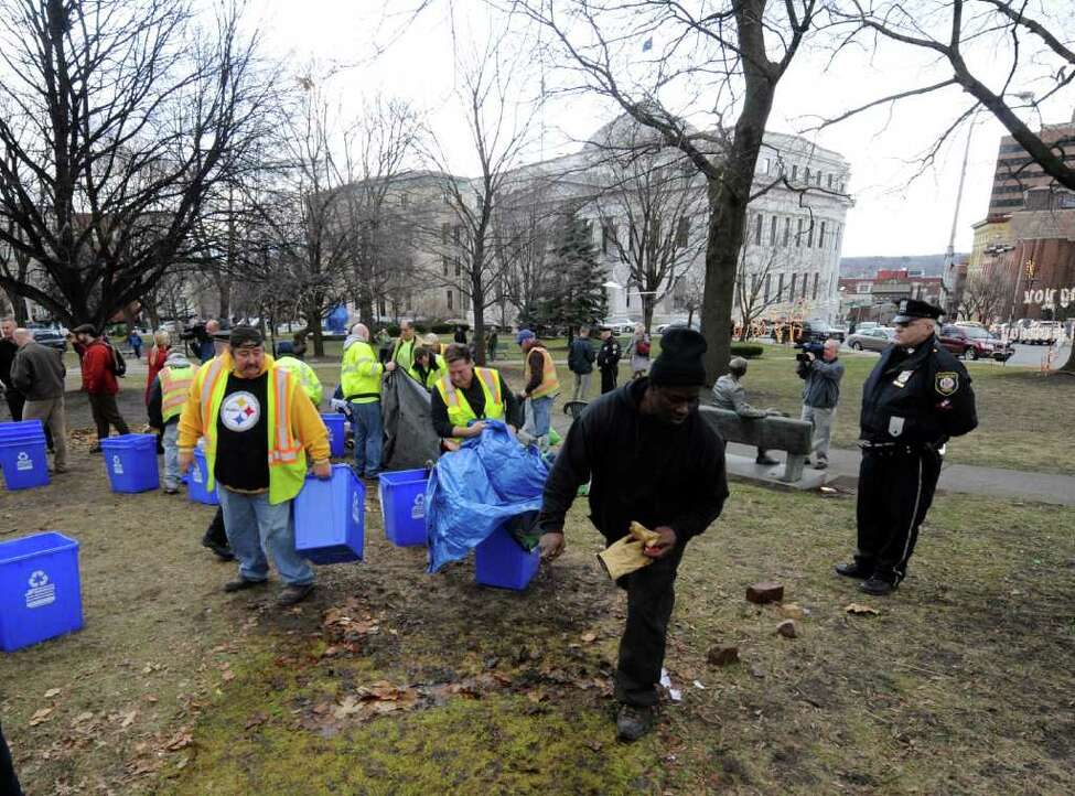 Under the watchful eye of the Albany Police members of the Albany Department of General Services remove the tents and anything related to the encampment of Occupy Albany from Academy Park in Albany, N.Y. Dec. 22, 2011. (Skip Dickstein / Times Union)