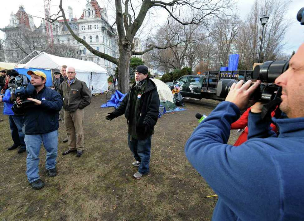 A protester yells at the police forensics investigators for making his photograph as members of the Albany Department of General Services remove the tents and anything related to the encampment of Occupy Albany from Academy Park in Albany, N.Y. Dec. 22, 2011. (Skip Dickstein / Times Union)