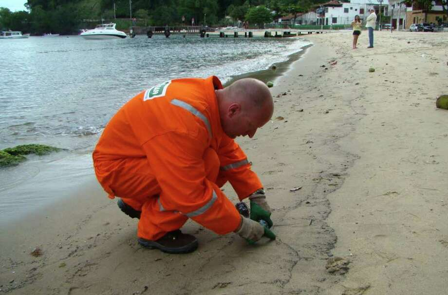 PAULO ROBERTO: ASSOCIATED PRESS/AGENCIA O GLOBO  MEASURING DAMAGE: An environmental technician in Brazil this week collects samples of sand from a beach that shows a large stain in Angra dos Reis. A leak from a Japanese-operated rig could affect the area, a Brazilian official said. Photo: Paulo Roberto Araujo / AGENCIA O GLOBO