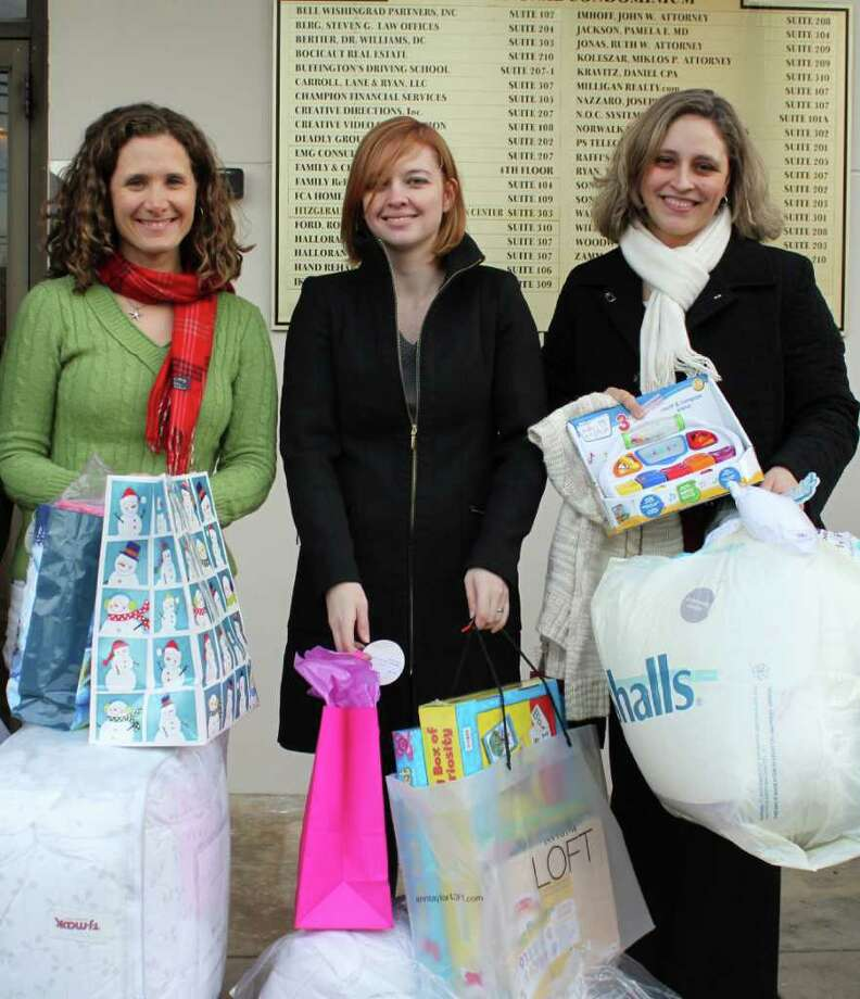 Left to right, Kathleen Callahan and Laura Jacob of FactSet Research Systems Inc. in Norwalk, along with Mayx Holmes, manager of volunteer services at Family & Childrenís Agency, carry in some of the many gifts donated by employees of Fact Set. Photo: Contributed Photo