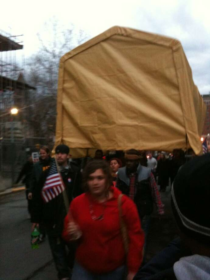 Occupy Albany members carry their information tent up State Street in Albany on Thursday, Dec. 22, 2011. (Bryan Fitzgerald/Times Union)